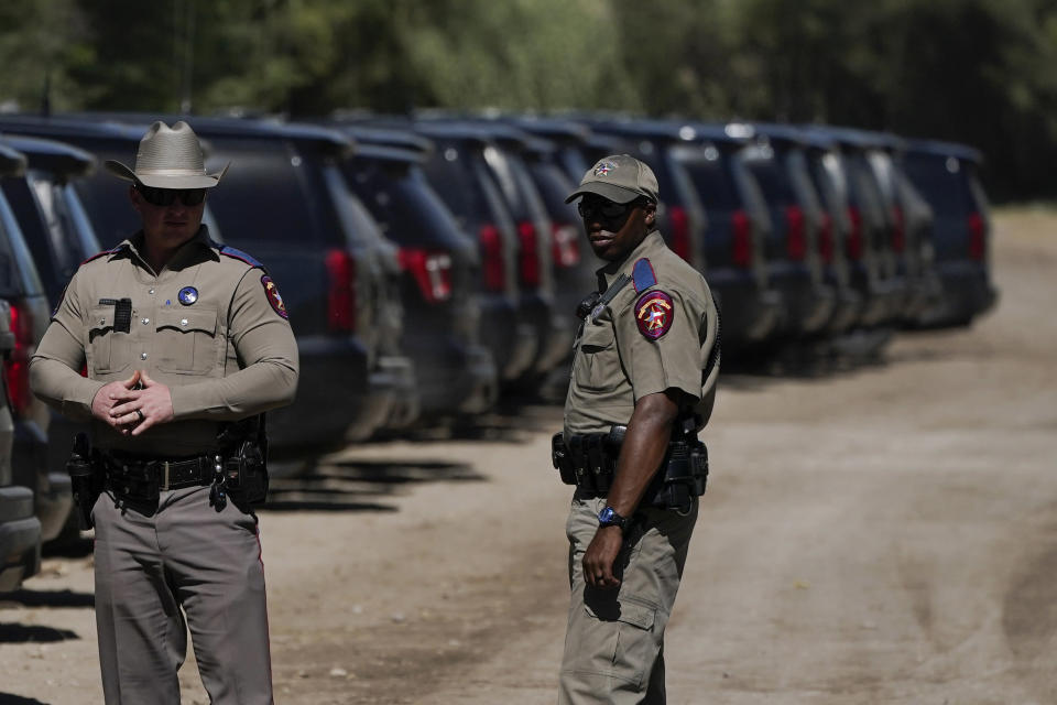 """Texas Department of Public Safety officials stand near a lineup or vehicles parked near an encampment under the Del Rio International Bridge where migrants, many from Haiti, have been staying after crossing the Rio Grande, Thursday, Sept. 23, 2021, in Del Rio, Texas. The """"amistad,"""" or friendship, that Del Rio, Texas, and Ciudad Acuña, Mexico, celebrate with a festival each year has been important in helping them deal with the challenges from a migrant camp that shut down the border bridge between the two communities for more than a week. Federal officials announced the border crossing would reopen to passenger traffic late Saturday afternoon and to cargo traffic on Monday. (AP Photo/Julio Cortez)"""