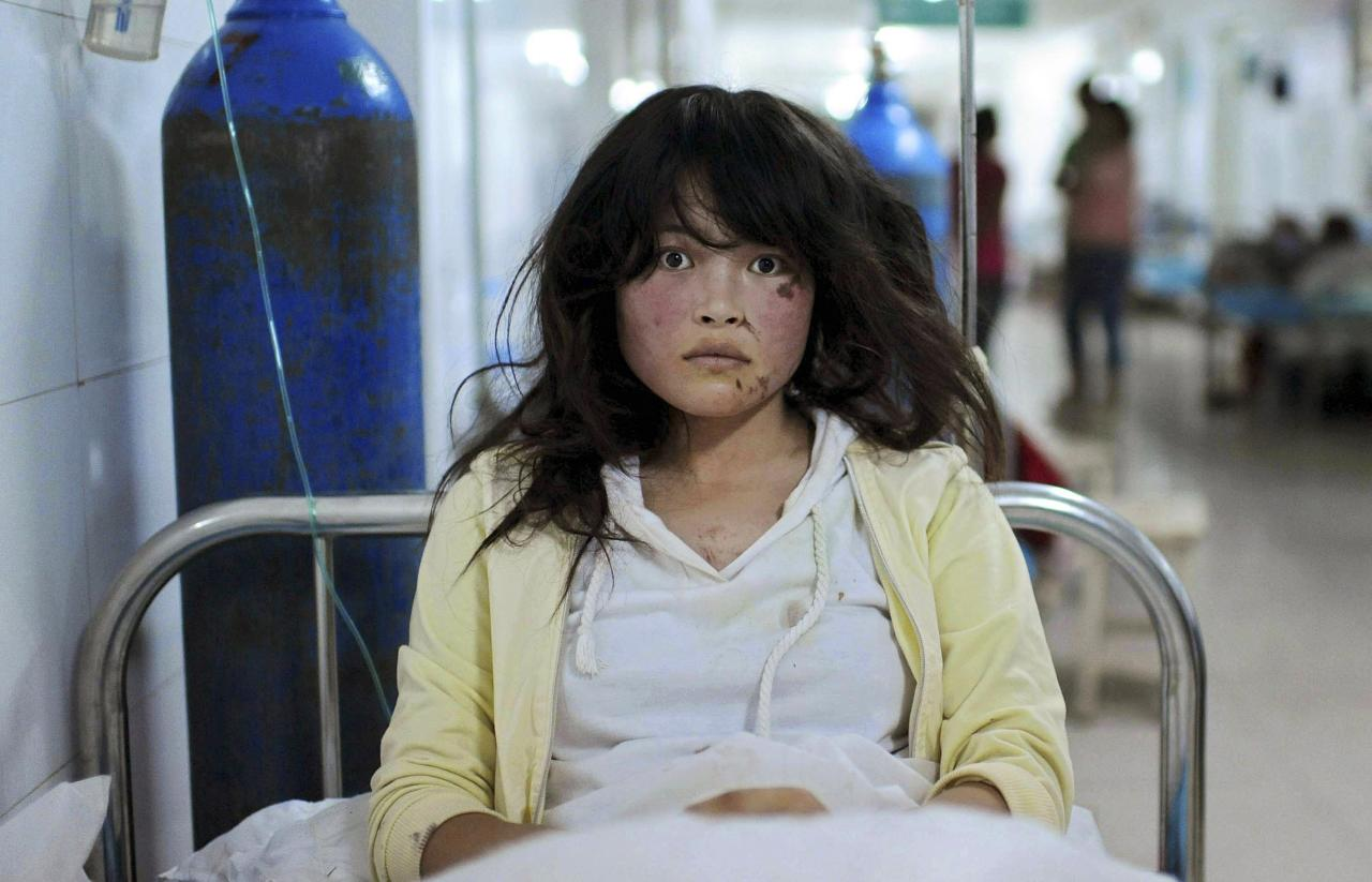 RNPS - PICTURES OF THE YEAR 2013 - Song Xuxia, 19, receives treatment at a hospital after a 6.6 magnitude earthquake hit Minxian county, Dingxi, Gansu province July 23, 2013. The death toll from two earthquakes in China's western Gansu province has climbed to 95, with more than 1000 people injured, after around 51,800 buildings collapsed and tens of thousands more were badly damaged. Song's leg, waist and face were injured during the earthquake when she was stuck in a collapsed house. Fortunately the villagers heard her cry and managed to pull her out from the debris in time, according to local media. REUTERS/Stringer (CHINA - Tags: DISASTER HEALTH TPX) CHINA OUT. NO COMMERCIAL OR EDITORIAL SALES IN CHINA