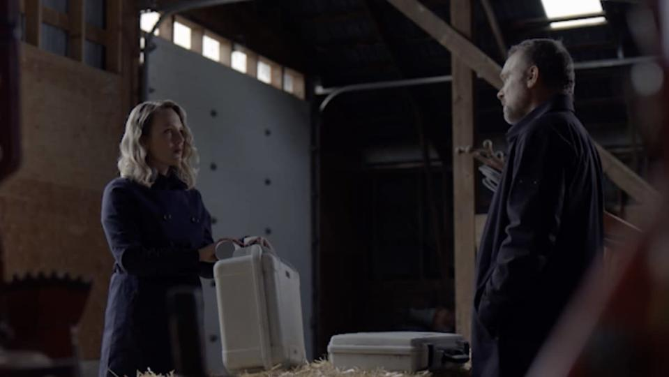 A blonde woman holds a white case as a man with a case in front of him on hay in a barn looks at her