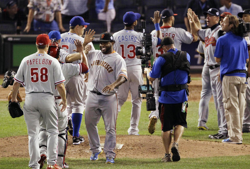 National League's Pablo Sandoval, of the San Francisco Giants, right, celebrates with teammates after their 8-0 win over the American League in the MLB All-Star baseball game, Tuesday, July 10, 2012, in Kansas City, Mo. (AP Photo/Charlie Neibergall)