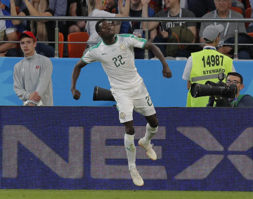 Senegal's Moussa Wague, right, celebrates his side's 2nd goal during the group H match between Japan and Senegal at the 2018 soccer World Cup at the Yekaterinburg Arena in Yekaterinburg , Russia, Sunday, June 24, 2018. (AP Photo/Vadim Ghirda)
