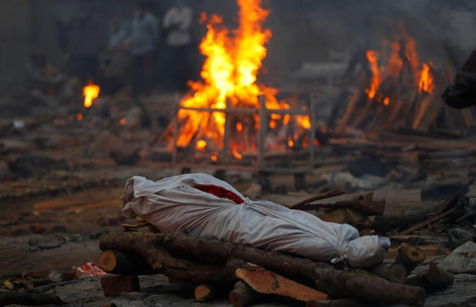 """<div class=""""inline-image__caption""""><p>The body of someone who died from COVID-19 lies on a funeral pyre during a mass cremation, at a crematorium in New Delhi, India May 1, 2021. </p></div> <div class=""""inline-image__credit"""">REUTERS/Adnan Abidi</div>"""