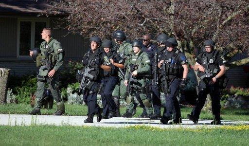 Law enforcement personnel walk near the Sikh Temple of Wisconsin