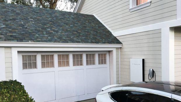 A home garage with white doors and dark grey roof tiles are shown. Part of a white Tesla car is seen in driveway.