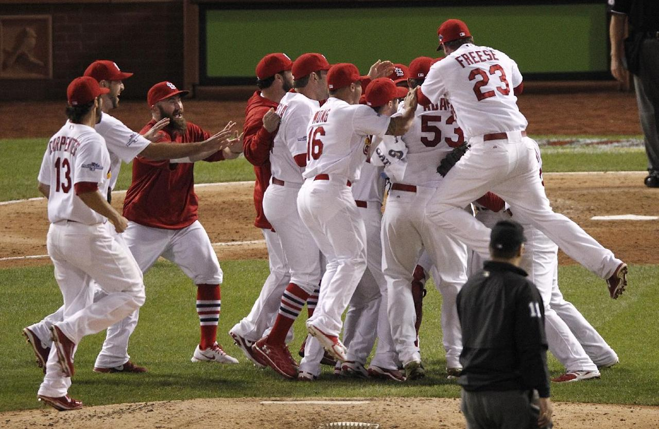 The St. Louis Cardinals celebrate after beating the Pittsburgh Pirates 6-1 in Game 5 of a National League baseball division series, Wednesday, Oct. 9, 2013, in St. Louis. The Cardinals advanced to the NL championship series against the Los Angeles Dodgers. (AP Photo/Sarah Conard)