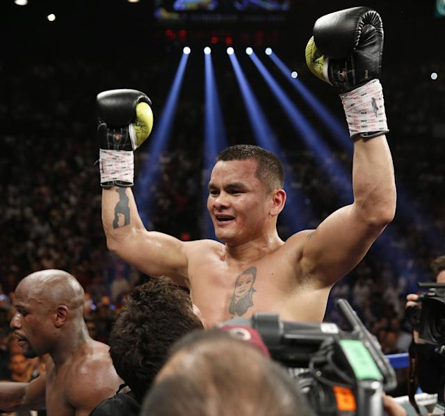 Marcos Maidana, from Argentina, celebrates at the end of his WBC-WBA welterweight title boxing fight against Floyd Mayweather Jr., lower left, Saturday, May 3, 2014, in Las Vegas. Mayweather won the bout by majority decision. (AP Photo/Eric Jamison)