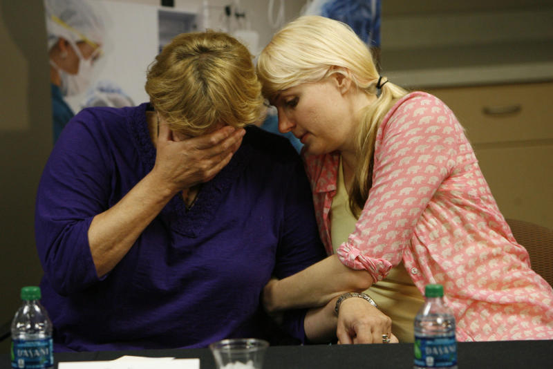 Tara Evans, left, is comforted by her daughter Karen Evans during a news conference at the McKay-Dee Hospital Center in Ogden, Utah on Monday, June 17, 2013, to update the condition of Tara's husband, James Evans, who was shot in the head during church services on Sunday. James Evans, 65, was in critical condition Monday, but has made steady progress, said intensive care unit director Dr. Barbara Kerwin. (AP Photo/The Salt Lake Tribune, Francisco Kjolseth)  DESERET NEWS OUT; LOCAL TV OUT; MAGS OUT