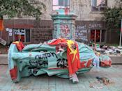 <p>The toppled statue of Egerton Ryerson, one of the architects of indigenous boarding school system, is laying on its side in Toronto on June 6, 2021. (Photo by OLIVIER MONNIER/AFP via Getty Images)</p>