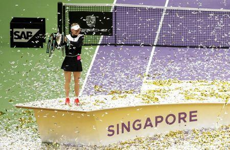 Tennis - WTA Tour Finals - Singapore Indoor Stadium, Singapore - October 29, 2017 Denmark's Caroline Wozniacki celebrates with the trophy after winning the final against USA's Venus Williams REUTERS/Jeremy Lee