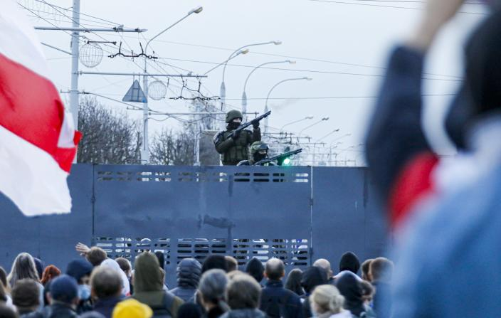 Belarusian riot police stand guard on top of a police barricade blocking a street during an opposition rally to protest the official presidential election results in Minsk, Belarus, Sunday, Oct. 25, 2020. The demonstrations were triggered by official results giving President Alexander Lukashenko 80% of the vote in the Aug. 9 election that the opposition insists was rigged. Lukashenko, who has ruled Belarus with an iron fist since 1994, has accused the United States and its allies of fomenting unrest in the ex-Soviet country. (AP Photo)