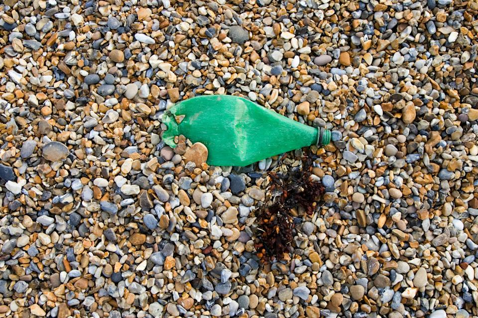 Plastic bottle discarded on pebbly beach next to seaweed