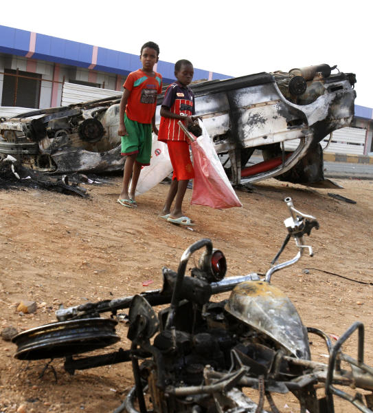 Sudanese boys walk amid burned vehicles after rioters torched a fuel station in Khartoum, Sudan, Thursday, Sept. 26, 2013. Sudanese authorities have deployed troops around vital installations and gas stations in Khartoum following days of deadly rioting over gas price hikes. (AP Photo/Abd Raouf)