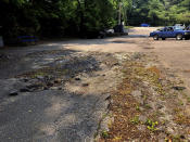 A crumbling parking lot at the Prestera Center headquarters is shown Wednesday, July 21, 2021 in Huntington, W. Va. In one of the epicenters of the U.S. opioid explosion, the nonprofit mental health and addiction treatment provider really could use some money. Whether from a potential national settlement deal with big U.S. drug distribution companies or from some other source, an infusion of cash would help stem the tide of losses in staffing and other areas in recent years, along with the strain caused by the coronavirus pandemic. (AP Photo/John Raby)