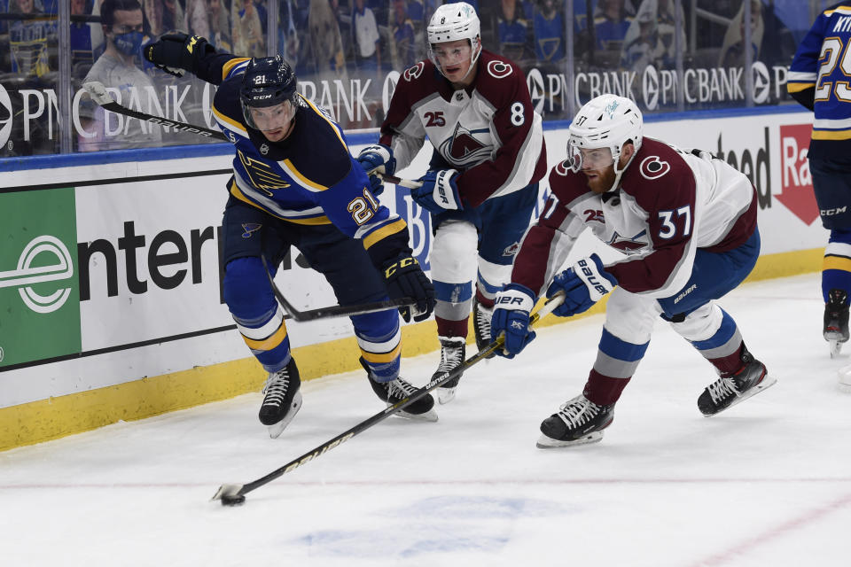 St. Louis Blues' Tyler Bozak (21) and Colorado Avalanche's J.T. Compher (37) battle for the puck during the second period of an NHL hockey game on Wednesday, April 14, 2021, in St. Louis. (AP Photo/Joe Puetz)