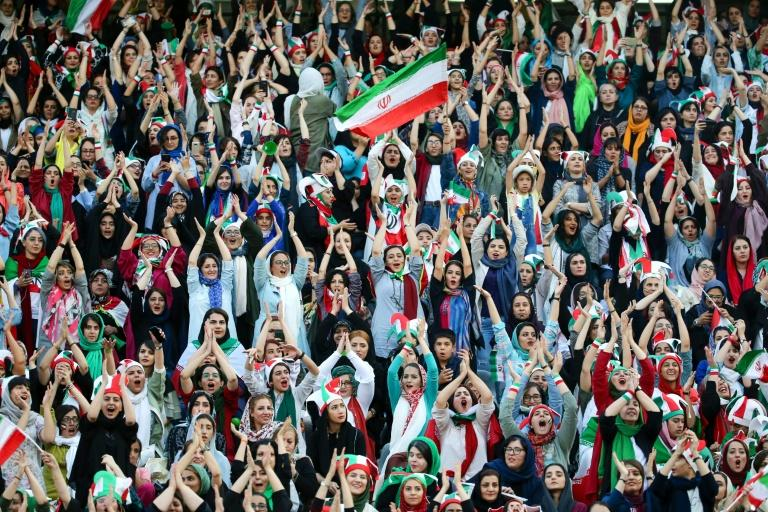 Wearing sporty hats and the national flag, Iranian women cheer for their team at a game they will never forget