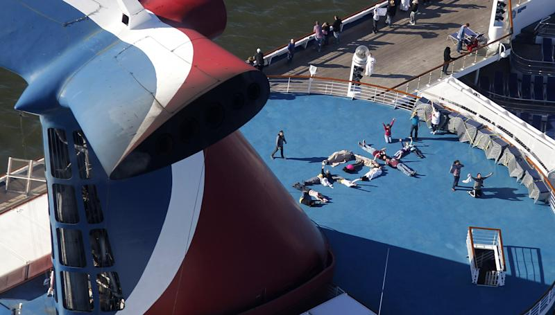 """FILE - In this Thursday, Feb. 14, 2013, file photo, passengers spell out the word """"HELP"""" aboard the disabled Carnival Lines cruise ship Triumph as it is towed to harbor off Mobile Bay, Ala. Cruise operators, like airline pilots, may be relying too heavily on electronics to navigate massive ships, losing the knowledge and ability needed to operate a vessel in the case of a power failure, an expert sea pilot told a federal agency on Wednesday. (AP Photo/Gerald Herbert, File)"""