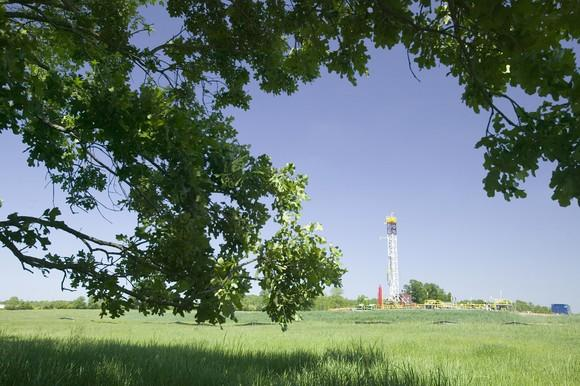 Drilling rig in the background in a green field with a low-hanging tree in the foreground.