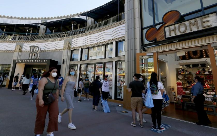 ANAHEIM, CALIF. - JULY 9, 2020. Visitors wait in a long iine to access a shop as Downtown Disney reopens on Thursday, July 9, 2020. Officials required visitors to wear face coverings and practice social distancing. By 5:00 p.m. security guards closed the parking gate, saying that the shopping and dining complex had reached its capacity. Disney''s adjacent them parks remain closed. (Luis Sinco/Los Angeles Times)