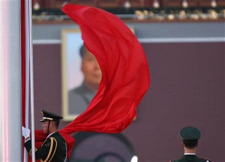 A paramilitary policeman holds the Chinese national flag at a flag lowering ceremony on Tiananmen square next to the Great Hall of the People, where the closing ceremony of the Chinese Communist Party plenum is going to be held on Tuesday, as the portrait of late Chinese Chairman Mao Zedong is seen in the background in Beijing, November 11, 2013. REUTERS/Kim Kyung-Hoon