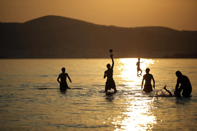<p>People enjoy the sea during sunset in the outskirts of Izmir, western Turkey, Thursday, Aug. 23, 2018. (AP Photo/Emre Tazegul) </p>