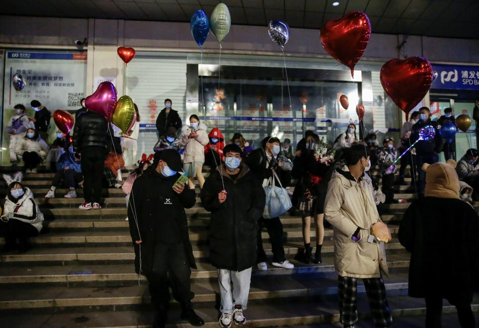 People hold balloons as they gather to celebrate the arrival of the new year in Wuhan (Reuters)