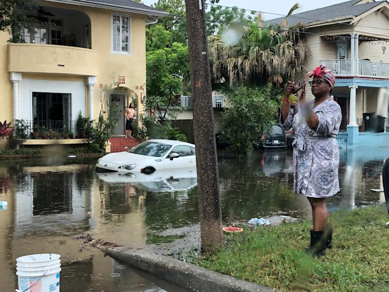 A woman stands photographing the scene in a flooded street in New Orleans, Louisiana, July 10, 2019. (Photo: Ryan Pasternak/Reuters)