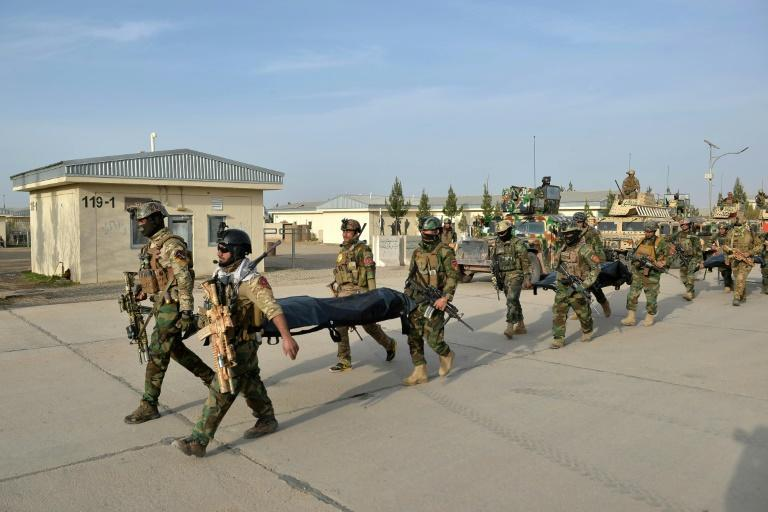Afghan National Army (ANA) commandos carry the dead bodies of Taliban fighters after a military operation in the Guzra district of Herat province on March 16, 2021