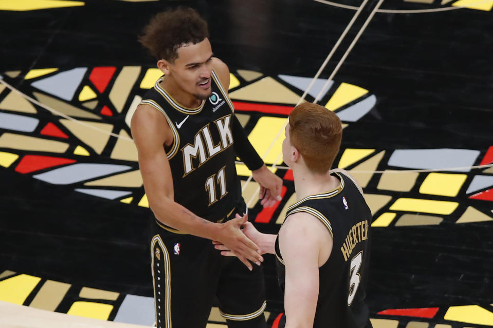 Atlanta Hawks guard Trae Young (11) reacts with guard Kevin Huerter (3) during the second half of the team's NBA basketball game against the Toronto Raptors on Saturday, Feb. 6, 2021, in Atlanta. (AP Photo/Todd Kirkland)