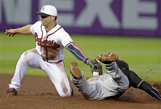 Atlanta Braves' Dan Uggla, left, loses the ball as he attempts to tag out Miami Marlins' Marcell Ozuna on a steal at second base in the fourth inning of a baseball game, Thursday, July 4, 2013, in Atlanta. (AP Photo/David Goldman)