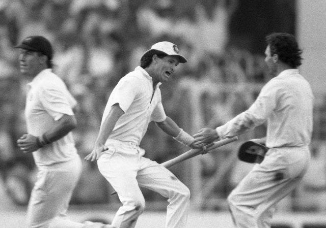 Dean Jones holds the stumps as he races to embrace Allan Border