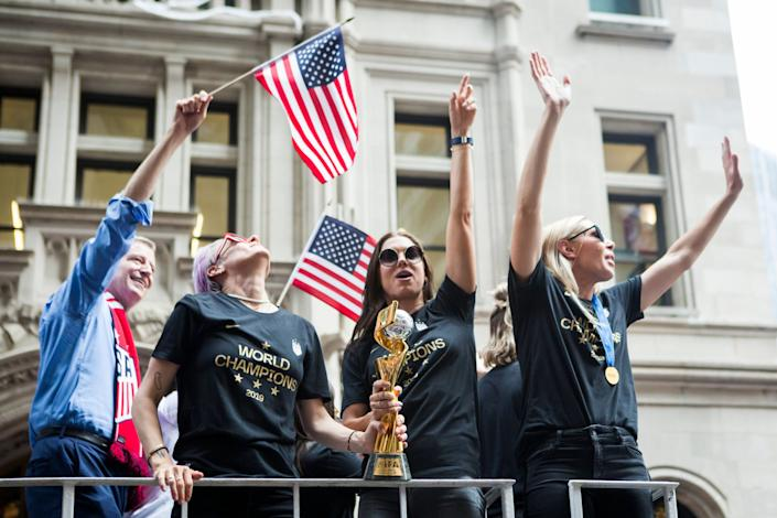Alex Morgan, center, holds the World Cup trophy with teammate Megan Rapinoe at the parade. (Photo: Ira L. Black - Corbis via Getty Images)