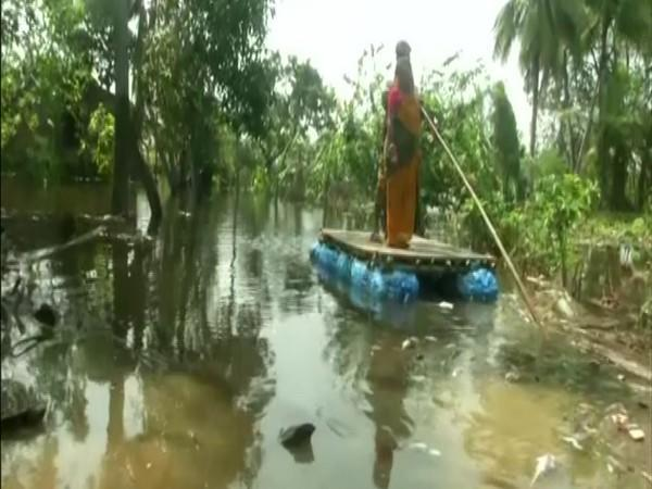 Villagers use handmade rafts for commute in submerged villages in WB's East Midnapore (photo/ANI)