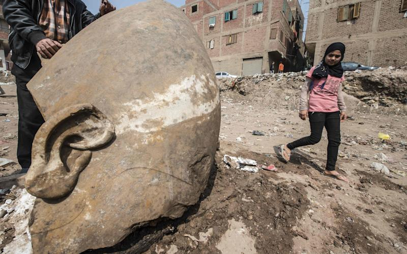 An Egyptian girl walks past the head of the statue unearthed in Cairo - Credit: AFP