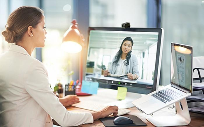 Woman sitting at a desk in front of a computer screen showing another woman.