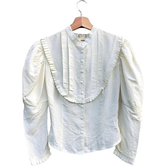 """<br><br><strong>Gunne Sax</strong> '70s White Ruffled Bib and Puff Sleeve Blouse, $, available at <a href=""""https://go.skimresources.com/?id=30283X879131&url=https%3A%2F%2Fshopthrilling.com%2Fcollections%2Fclothing%2Fproducts%2F70s-white-ruffled-bib-and-puff-sleeve-blouse-by-gunne-sax"""" rel=""""nofollow noopener"""" target=""""_blank"""" data-ylk=""""slk:Thrilling"""" class=""""link rapid-noclick-resp"""">Thrilling</a>"""