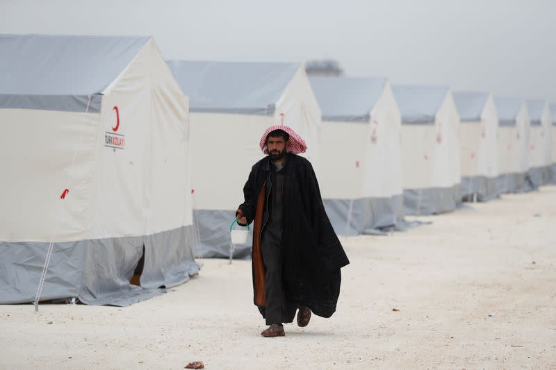 FILE PHOTO: A displaced Syrian man walks past by tents supplied by Turkish Red Crescent at Kelbit camp in Idlib province