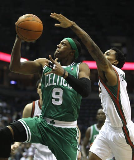 Boston Celtics' Rajon Rondo (9) drives past Milwaukee Bucks' Brandon Jennings, right, during the first half of an NBA basketball game on Thursday, March 22, 2012, in Milwaukee. (AP Photo/Jeffrey Phelps)