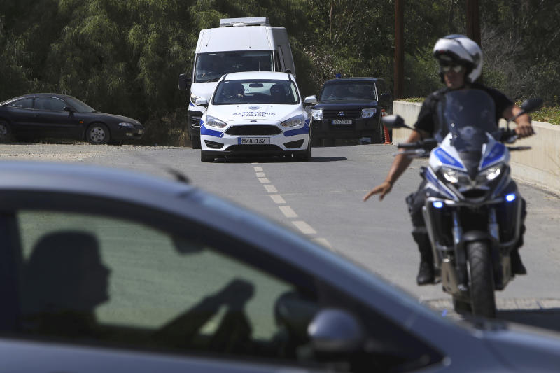 """A motorcyclist police officer escorts and guards the police van carrying Army Captain Nicholas Metaxas from the court to the Cypriot central prison in capital Nicosia, Cyprus, Monday, June 24, 2019.  A Cypriot army captain on Monday tearfully apologized to the families of seven foreign women and girls for the """"unjust pain"""" he has caused them after pleading guilty to a dozen charges of premeditated murder and kidnapping.  (AP Photo/Petros Karadjias)"""