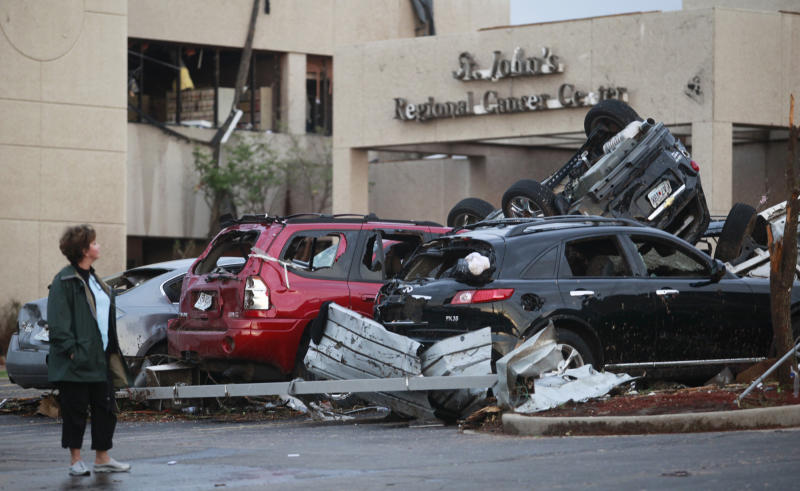 A woman looks at the damage to St. John's Regional Medical Center in Joplin, Mo., Monday, May 23, 2011, a day after it was hit by a tornado. Authorities warned Monday that the death toll could climb as search and rescue workers continued their efforts. (AP Photo/The Wichita Eagle, Jaime Green)