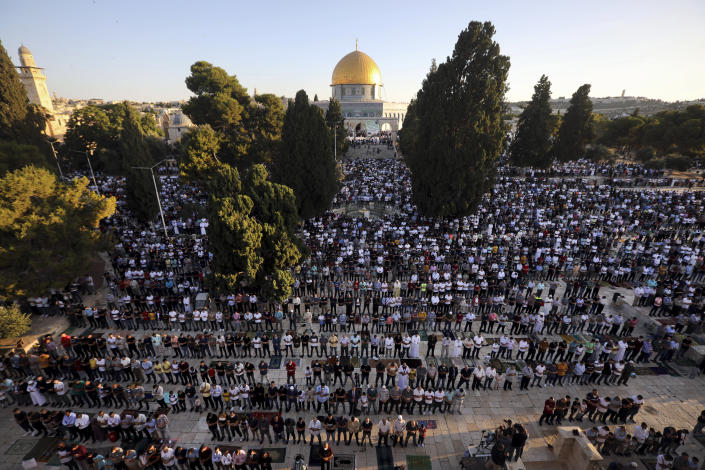 Muslim men offer Eid al-Adha prayer next to the Dome of the Rock Mosque in the Al Aqsa Mosque compound in Jerusalem's old city, Friday, July 31, 2020. This is the first Feast of Sacrifice since the onset of the global coronavirus pandemic. The major Muslim holiday, at the end of the hajj pilgrimage to Mecca, is observed around the world by believers and commemorates prophet Abraham's pledge to sacrifice his son as an act of obedience to God. (AP Photo/Mahmoud Illean)