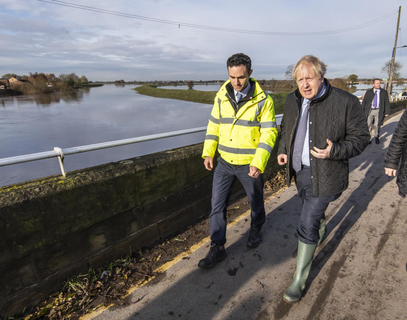Prime Minister Boris Johnson walks with Oliver Harmar, the Yorkshire Area Director of the Environment Agency during a visit to Stainforth, Doncaster, to see the recent flooding. (PA Images)