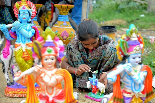 <p>A hawker gives the finishing touches to a Plaster Of Paris (POP) idol of Hindu deity Krishna at a road side stall in Bangalore on August 31, 2018. – 'Krishna Janmashtami' is an annual festival that celebrates the birth of Hindu deity Krishna. (Photo by MANJUNATH KIRAN/AFP/Getty Images) </p>