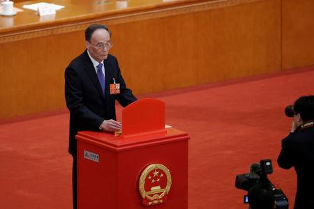 Wang Qishan, former secretary of the Central Commission for Discipline Inspection, drops his ballot during a vote at the fifth plenary session of the National People's Congress (NPC) at the Great Hall of the People in Beijing, China March 17, 2018.  REUTERS/Jason Lee