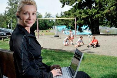 woman on laptop with phone headset while kids play in garden