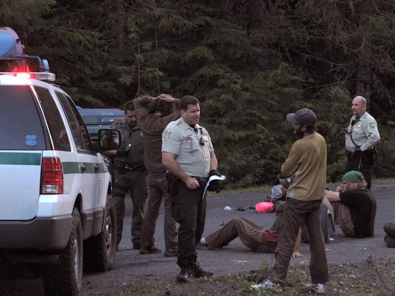 In a June 21, 2011 photo, several people are searched and questioned by U.S. Forest Service law enforcement officers after they were pulled over while driving to the Rainbow Family gathering in the Gifford Pinchot National Forest north of Stevenson, Wash.  Thousands will descend on the Gifford Pinchot National Forest for the 40th annual gathering of the Rainbow Family of Living Light, a group of peace activists borne out of the '60s counterculture movement. (AP Photo/Sahnnon Dininny)
