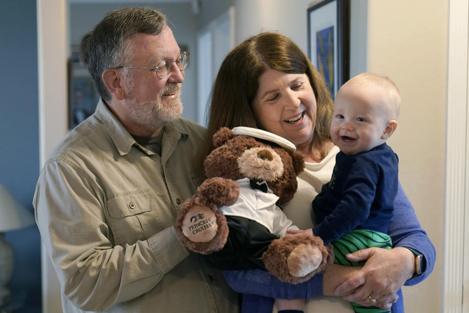 """John Miller, left, watches as his wife, Laurie, holds their grandson, Theo Hamilton, while being interviewed in San Jose, Calif., Wednesday, March 10, 2021. The Millers were passengers on the Grand Princess cruise ship, which had captured the world's attention in 2020 when it became clear the coronavirus pandemic had arrived at U.S. shores on board the boat. """"There was so much inconsistent information from day-to-day that it felt like we were guinea pigs,"""" Laurie Miller said. (AP Photo/Jeff Chiu)"""