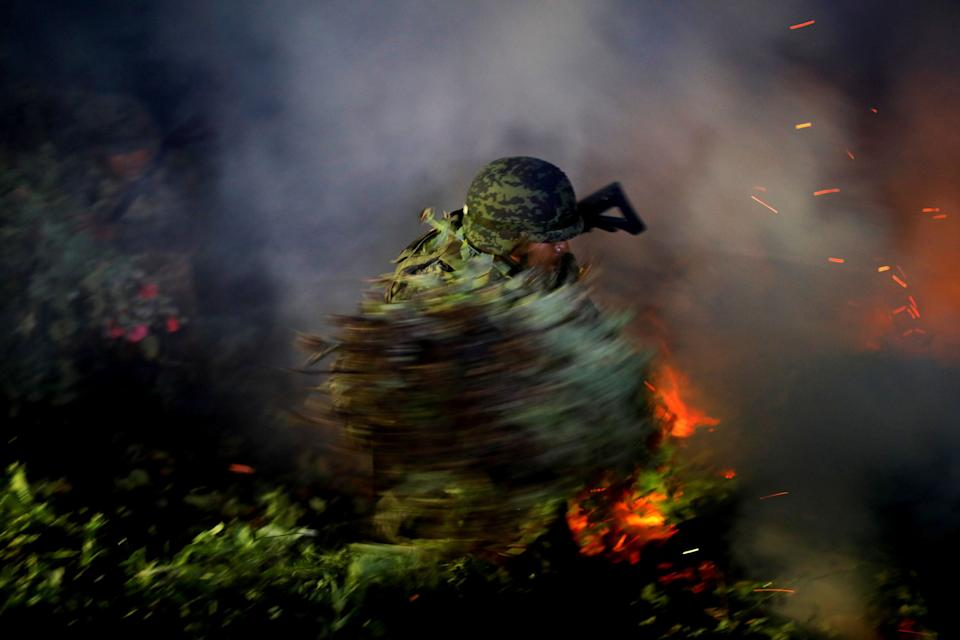A soldier burns an illegal opium plantation in Mexico