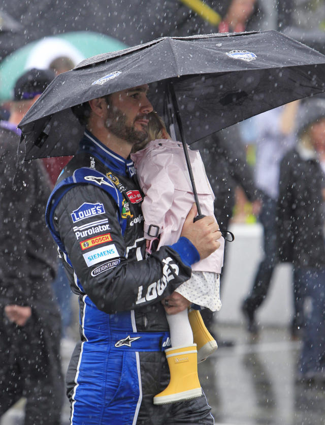 Jimmie Johnson walks along pit road with his daughter Genevieve, during a rain delay before the NASCAR Daytona 500 auto race at Daytona International Speedway in Daytona Beach, Fla., Sunday, Feb. 26, 2012. (AP Photo/John Raoux)