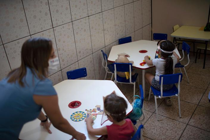 Children wear face shields and sit spaced apart at individual tables at the Pereira Agustinho day care, nursery school and preschool on July 6 in Duque de Caxias, in Rio de Janeiro's metropolitan region.