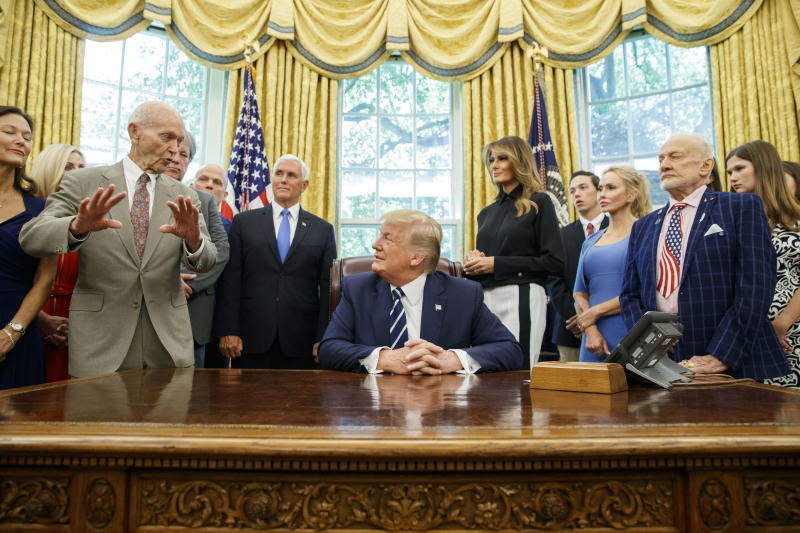 """FILE - In this Friday, July 19, 2019, file photo, President Donald Trump, center, listens to Apollo 11 astronaut Michael Collins, left, accompanied by Buzz Aldrin, Vice President Mike Pence and first lady Melania Trump, during a photo opportunity commemorating the 50th anniversary of the Apollo 11 moon landing, in the Oval Office of the White House in Washington. Collins, who circled the moon in the mother ship while Aldrin and Neil Armstrong planted a U.S. flag and gathered rocks, acknowledges that returning to the moon as a precursor to Mars is """"a valid plan."""" """"But I don't have to agree with it,"""" Collins said in an interview. """"I would take what I call the John F. Kennedy approach and I'd say if you want to go to Mars, you say you want to go to Mars and you go."""" (AP Photo/Alex Brandon, File)"""